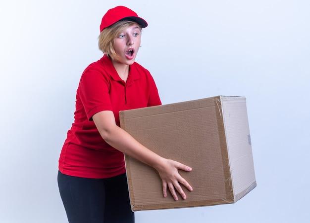 Sorpresa giovane ragazza delle consegne che indossa l'uniforme e il cappuccio che tiene la scatola isolata sul muro bianco