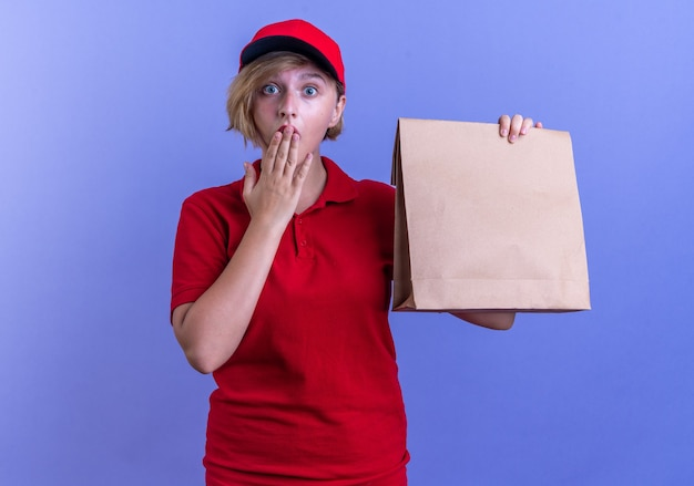 Sorpreso giovane ragazza delle consegne che indossa l'uniforme e il cappuccio che tiene il sacchetto di carta per alimenti ha coperto la bocca con la mano isolata sulla parete blu