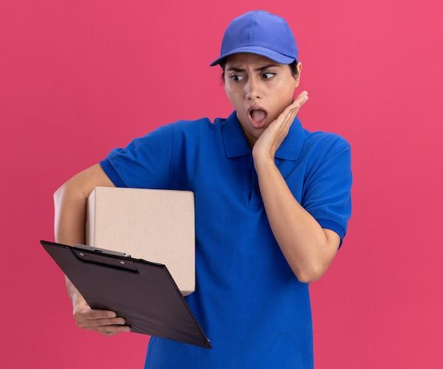 상자를 들고 분홍색 벽에 고립 된 뺨에 손을 넣어 그녀의 손에 클립 보드를보고 모자와 유니폼을 입고 놀란 젊은 배달 소녀