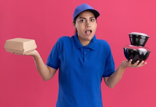 ピンクの壁に隔離された手を広げて食品容器を保持しているキャップと制服を着て驚いた若い配達の女の子