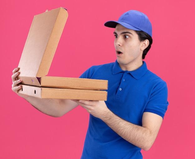 Sorpreso giovane fattorino in uniforme blu e cappuccio con pacchi di pizza che ne aprono uno che guarda al suo interno isolato su una parete rosa