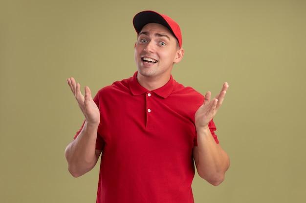 올리브 녹색 벽에 고립 된 유니폼과 모자 확산 손을 입고 놀란 젊은 배달 남자