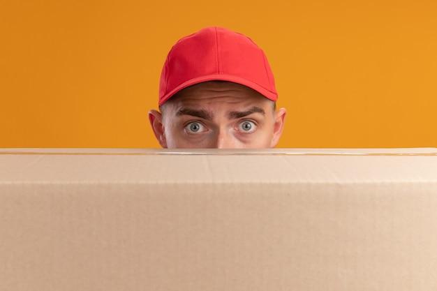 Giovane uomo di consegna sorpreso che indossa l'uniforme con il fronte coperto di protezione con la grande scatola isolata sulla parete arancione