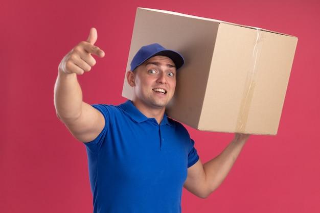 Удивленный молодой курьер в униформе с кепкой, держащий большую коробку на плече и показывающий вам жест, изолированный на розовой стене