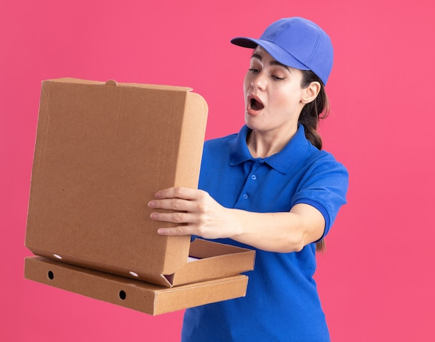 Удивленная молодая женщина-доставщик в униформе и кепке держит упаковки с пиццей, открывая одну, заглядывая внутрь