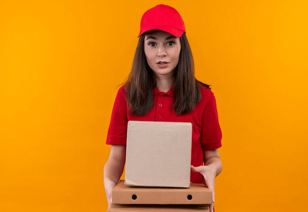 孤立した黄色の壁にボックスとピザの箱を保持している赤い帽子に赤いtシャツを着て驚いたの若い配達の女性