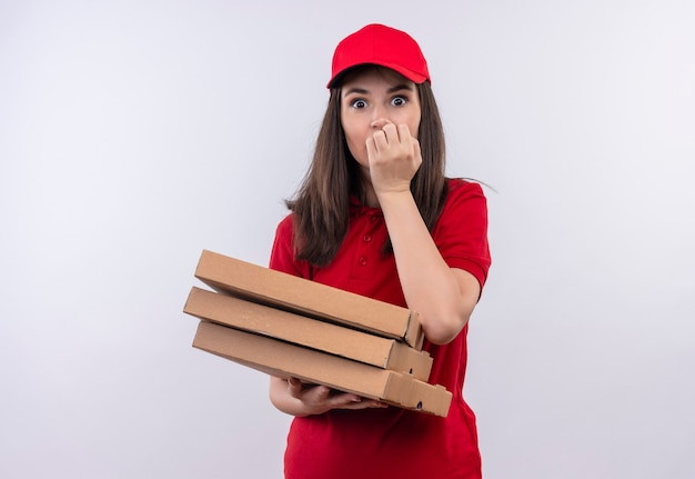 Surprised young delivery woman wearing red t-shirt in red cap holding a pizza box on isolated white wall