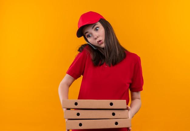 Giovane donna sorpresa di consegna che indossa la maglietta rossa in berretto rosso che tiene una scatola di pizza ee facendo una telefonata sulla parete arancione isolata