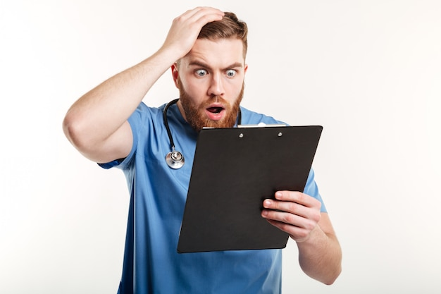 Surprised young doctor holding a clipboard and scratching his head