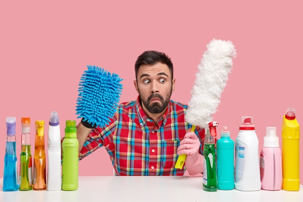 Surprised young european man carries brush for dust, wears checkered shirt, uses bottles of chemical supplies, astonished with much chores