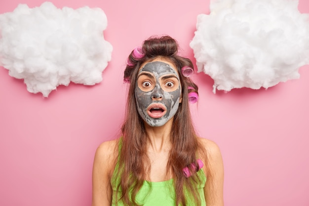 Удивленная молодая европейская женщина потрясенно смотрит в камеру, держит челюсть от удивления, делает прическу и проходит косметические процедуры, испугавшись опоздания на свидание, позирует в помещении