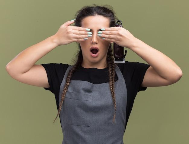 バリカンを持った制服を着た驚いた若い女性の床屋は、オリーブグリーンの壁に隔離された手で目を覆った