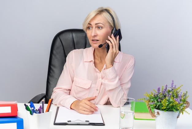 Sorpreso giovane operatore di call center femminile che indossa l'auricolare seduto al tavolo con strumenti da ufficio parla al telefono isolato su muro bianco