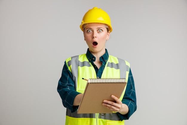 Giovane operaio edile femminile sorpreso che indossa il casco di sicurezza e la maglia di sicurezza che tiene il blocchetto per appunti che indica la matita su esso