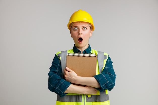 Sorpreso giovane operaio edile femminile che indossa il casco di sicurezza e giubbotto di sicurezza che abbraccia il blocco note