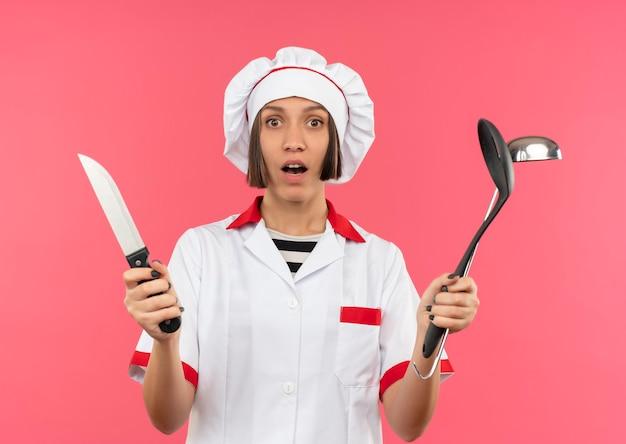 Удивленная молодая женщина-повар в униформе шеф-повара держит нож, лопатку и ковш, изолированные на розовой стене