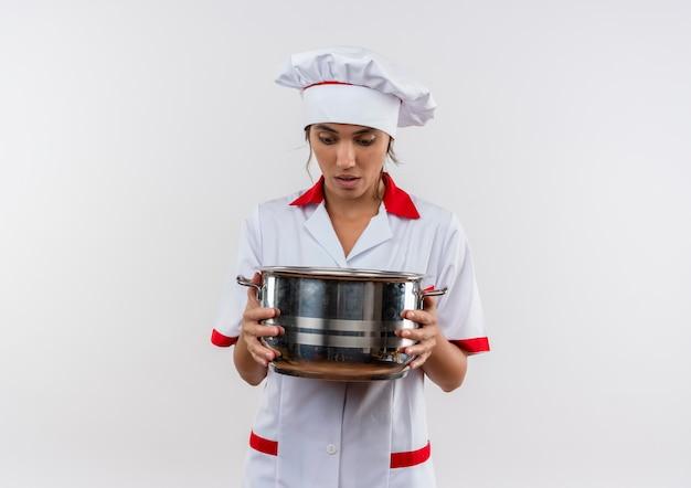 コピースペースのある鍋を持って見ているシェフの制服を着て驚いた若い女性料理人