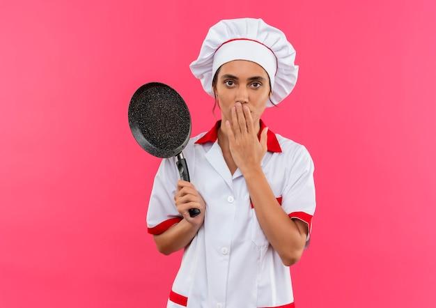 Giovane cuoco femminile sorpreso che indossa l'uniforme del cuoco unico che tiene la padella e la bocca coperta con la mano con lo spazio della copia