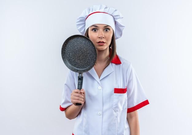 Удивленная молодая женщина-повар в униформе шеф-повара держит сковороду на белом фоне