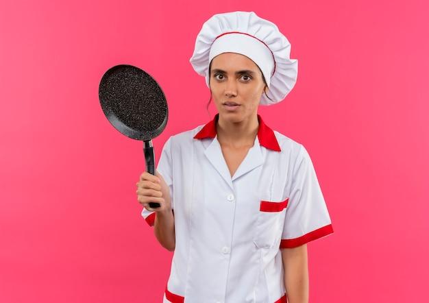 コピースペースでフライパンを保持しているシェフの制服を着て驚いた若い女性料理人