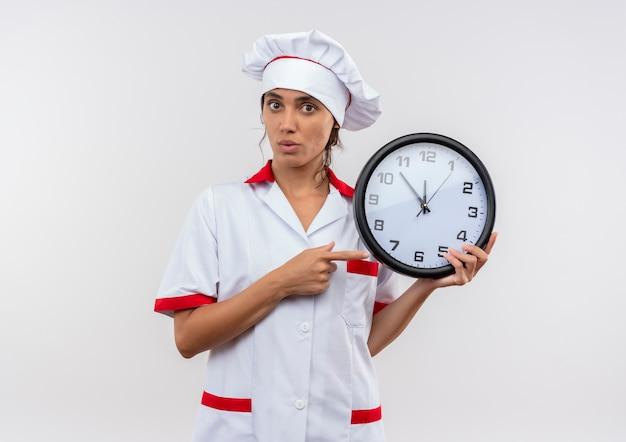 Giovane donna sorpresa che indossa la tenuta uniforme del cuoco unico e indica l'orologio da parete con lo spazio della copia