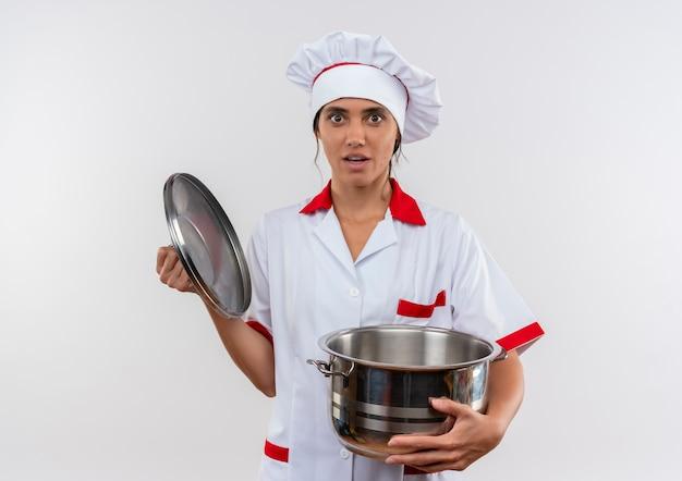 コピースペースと鍋と蓋を保持しているシェフの制服を着て驚いた若い女性料理人