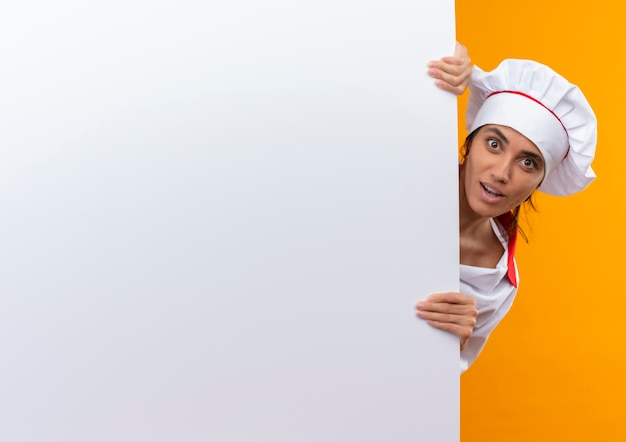 コピースペースで白い壁を保持しているシェフの制服を着て驚いた若い女性料理人