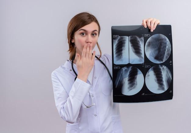 의료 가운과 청진기를 착용하고 복사 공간이 격리 된 흰 벽에 엑스레이 샷을 들고 놀란 젊은 여성 의사