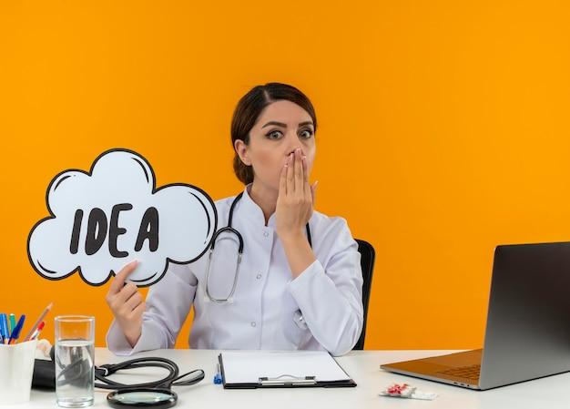 Удивленная молодая женщина-врач в медицинском халате и стетоскопе сидит за столом с медицинскими инструментами и ноутбуком, держа руку за рот, держа пузырь идеи, изолированный на желтой стене