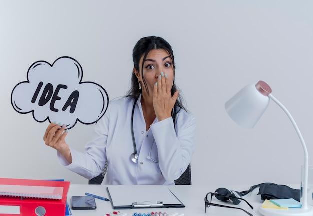 Удивленная молодая женщина-врач в медицинском халате и стетоскопе сидит за столом с медицинскими инструментами, держа пузырь идеи, глядя, кладя руку на изолированный рот