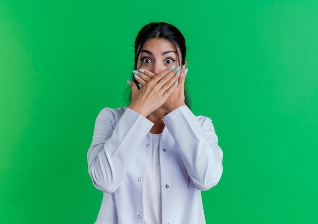 Giovane medico femminile sorpreso che indossa l'abito medico che copre la bocca con le mani isolate sulla parete verde con lo spazio della copia