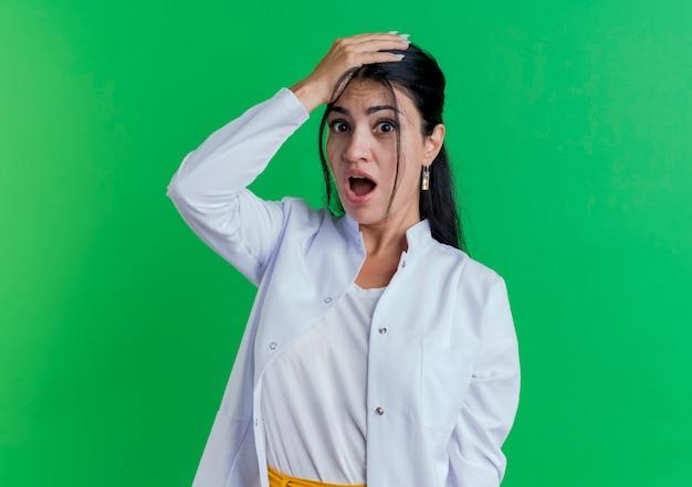 頭に手を置いて見ている医療ローブを着て驚いた若い女性医師