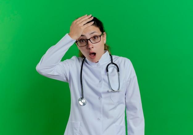 Giovane medico femminile sorpreso che indossa veste medica e stetoscopio e occhiali tenendo la mano sulla testa isolata sulla parete verde con lo spazio della copia