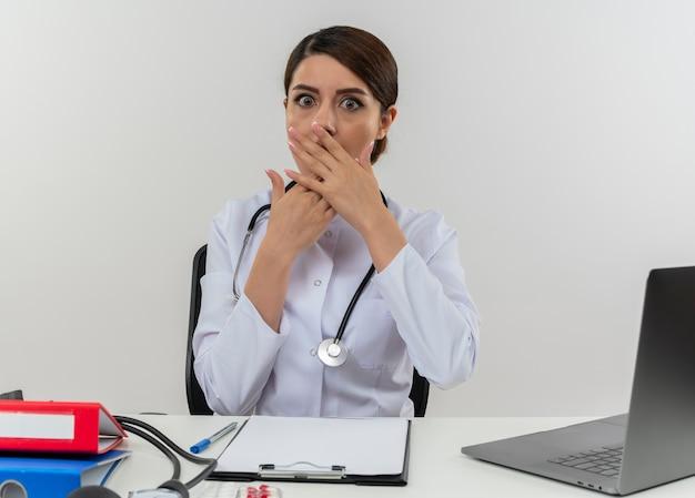Giovane medico femminile sorpreso che indossa veste medica e stetoscopio seduto alla scrivania con strumenti medici e computer portatile che mette le mani sulla bocca isolata sul muro bianco