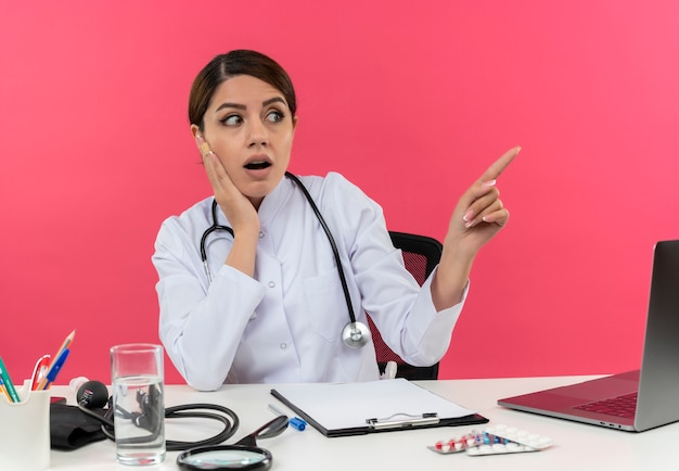 Surprised young female doctor wearing medical robe with stethoscope sitting at desk work on computer with medical tools holding hand on cheek and points to side on pink wall