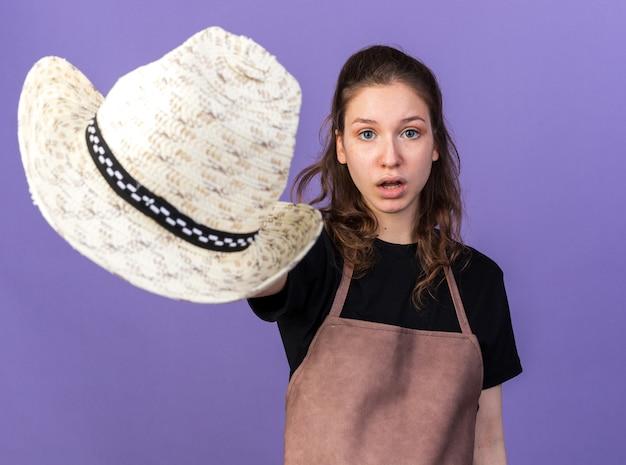 カメラでガーデニングの帽子を差し出している驚いた若い女性の庭師