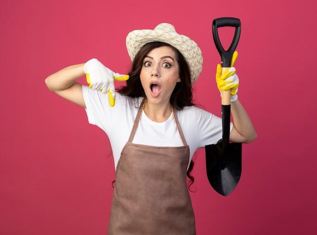 ガーデニングの帽子と手袋を身に着けている制服を着た驚いた若い女性の庭師は、ピンクの壁に隔離されたスペードとポイントを保持します