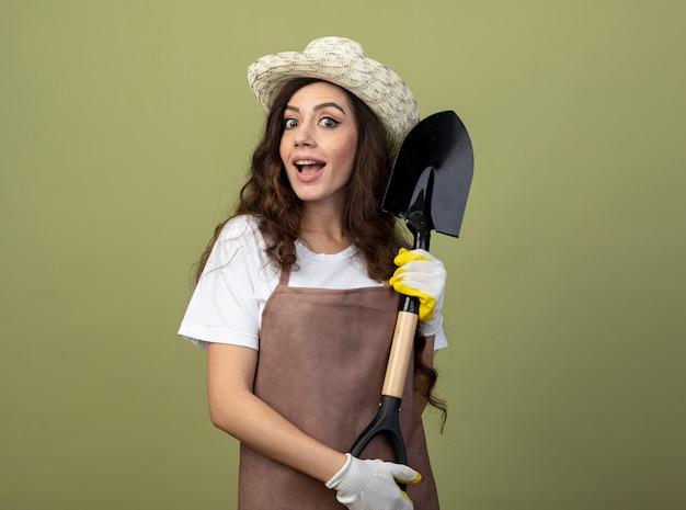 園芸帽子と手袋を身に着けている制服を着た驚いた若い女性の庭師は、オリーブグリーンの壁に隔離されたスペードを保持します