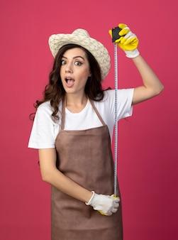 ガーデニング帽子と手袋を身に着けている制服を着た驚いた若い女性の庭師は、コピースペースでピンクの壁に巻尺を保持します