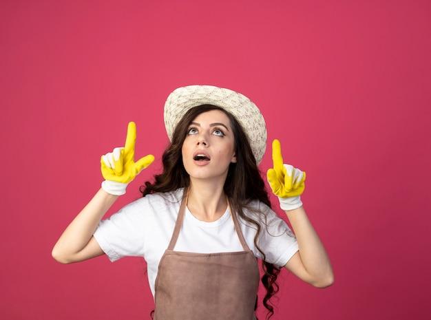 Удивленная молодая женщина-садовник в униформе в садовой шляпе и перчатках смотрит и указывает вверх изолированно на розовой стене