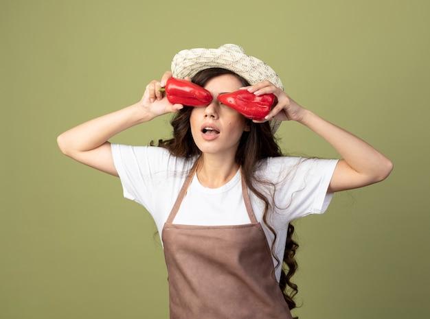 Удивленная молодая женщина-садовник в униформе в садовой шляпе прикрывает глаза красным перцем, изолированным на оливково-зеленой стене