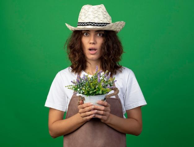植木鉢に花を保持している園芸帽子をかぶって制服を着た若い女性の庭師を驚かせた
