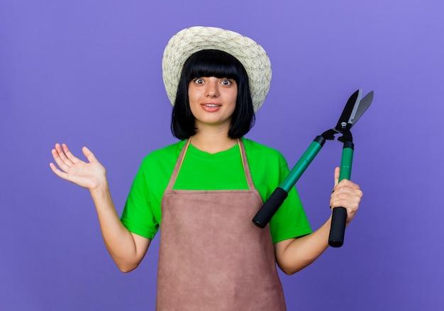 Удивленная молодая женщина-садовник в униформе в садовой шляпе держит машинку для стрижки