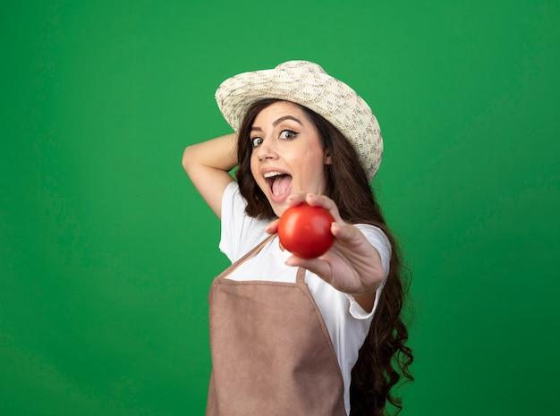 ガーデニング帽子をかぶって制服を着た驚いた若い女性の庭師は、緑の壁に隔離されたトマトを保持