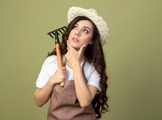 원예 모자를 쓰고 제복을 입은 놀란 젊은 여성 정원사는 턱에 손을 놓고 갈퀴를 보유하고 올리브 녹색 벽에 고립 된 찾고