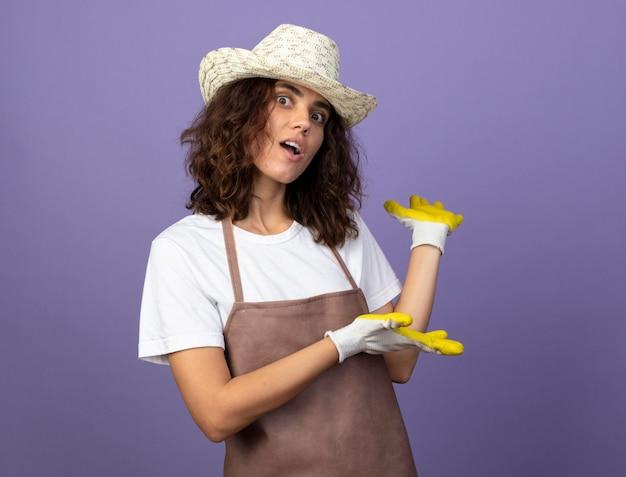 Il giovane giardiniere femminile sorpreso in uniforme indossa guanti e cappello da giardinaggio indica sul retro