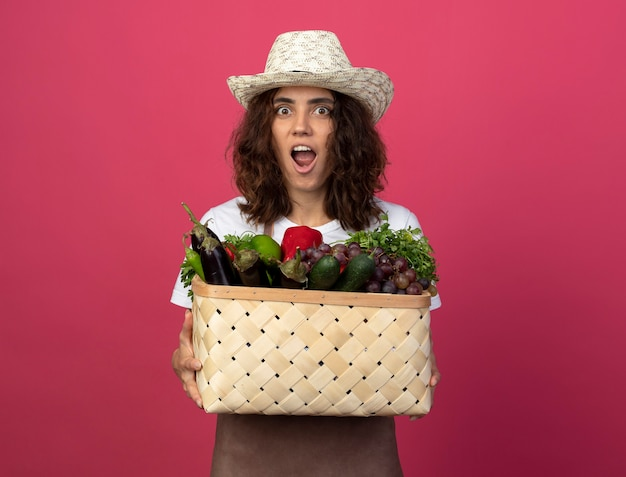 Surprised young female gardener in uniform wearing gardening hat holding vegetable basket