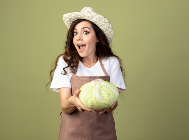Il giovane giardiniere femminile sorpreso in cappello da giardinaggio d'uso uniforme tiene il cavolo isolato sulla parete verde oliva