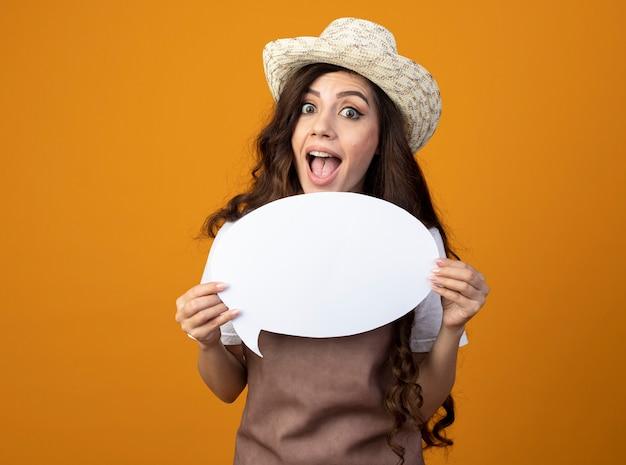 Il giovane giardiniere femminile sorpreso in cappello da giardinaggio d'uso uniforme tiene il fumetto isolato sulla parete arancio
