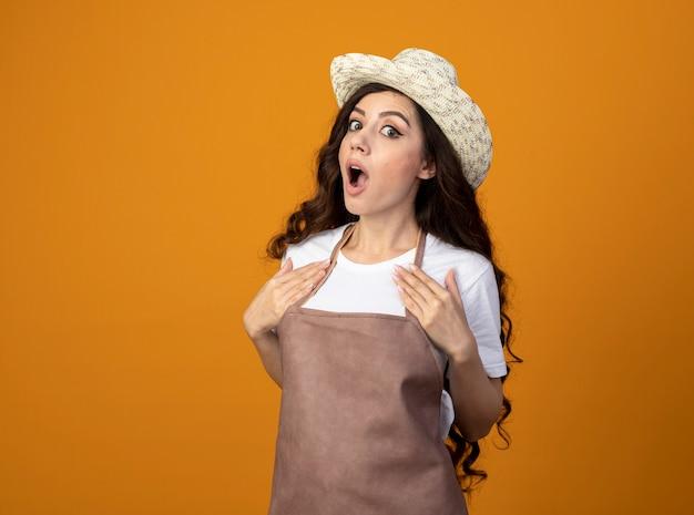 Il giovane giardiniere femminile sorpreso in cappello da giardinaggio d'uso uniforme mette le mani sul petto isolato sulla parete arancione